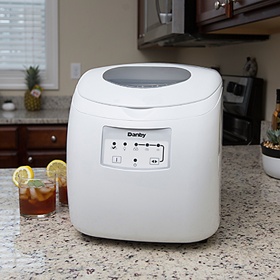 DANBY<sup>&reg;</sup> Portable Ice Maker - This portable ice maker produces up to 25lbs of ice a day.  Self-contained water reserve container means no drain or direct plumbing required.  Features simple electronic controls with LED display and self-clean function, transparent window on lid and ice scoop.